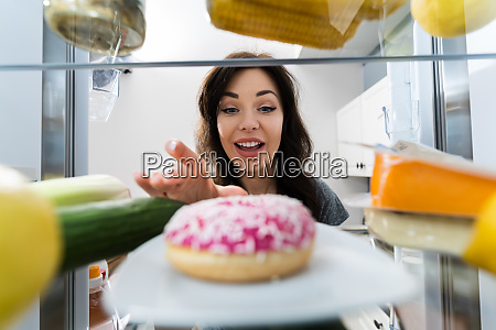 happy young woman taking donut from