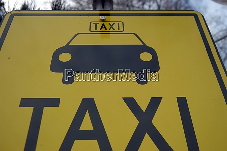 yellow taxi sign with pictogram of