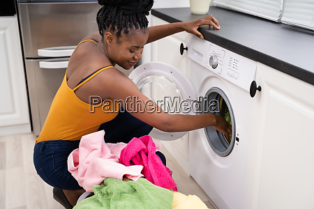woman loading dirty clothes in washing