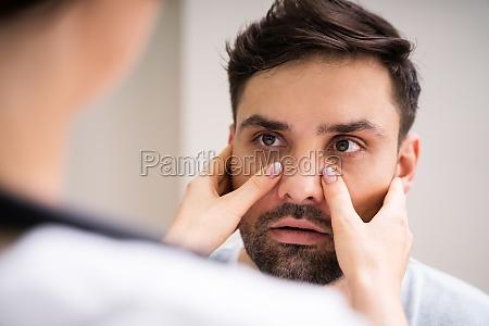 physician doctor doing sinusitis examination