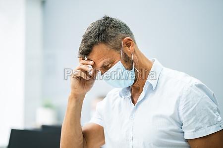 stressed employee in office wearing mask