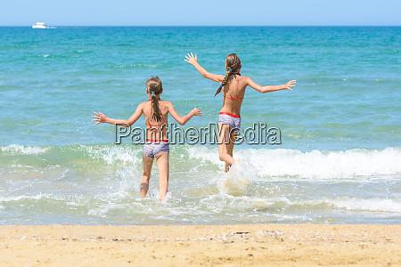 cheerful children run to swim in