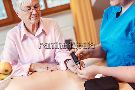 nurse administers diabetes test to senior