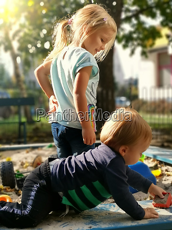 sister and brother playing with sand