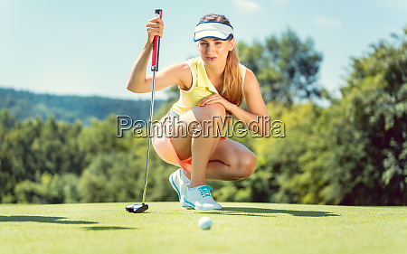 woman on golf course taking measure