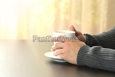 man hands holding a coffee cup