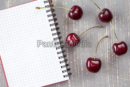 fresh cherries and blank notebook