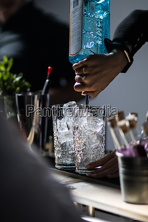 cocktail mixing barkeeper pouring gin mixing