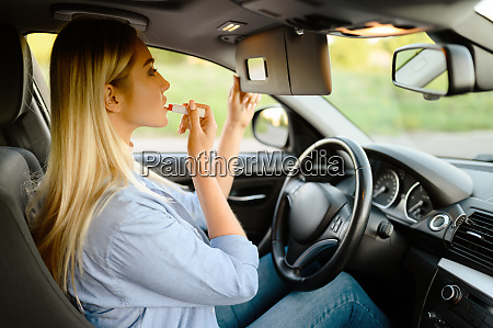 female student applies makeup driving school