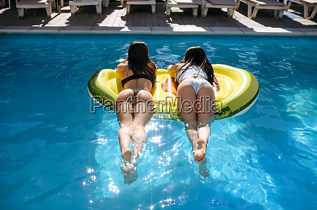 women in sunglasses sunbathing on mattress