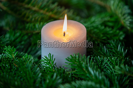 christmas motif with white burning candle