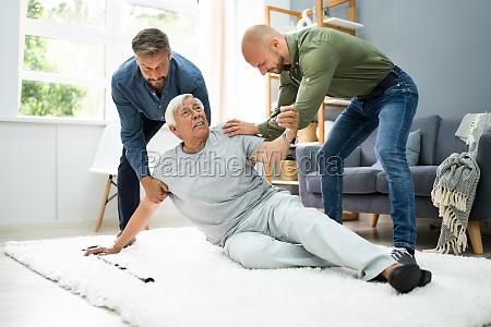 helping elder senior fallen man
