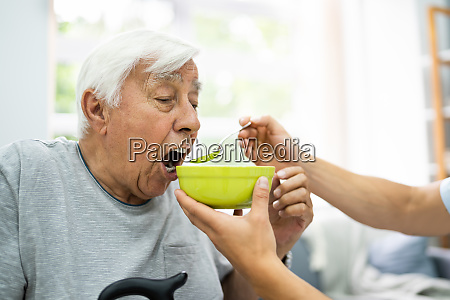 hungry elder patient being feed