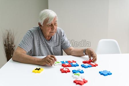 elder man playing jigsaw puzzle