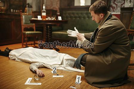 detective in gloves at crime scene
