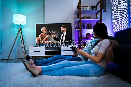family watching tv through tablet streaming