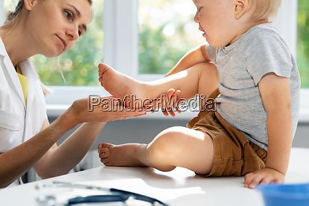 orthopedist podiatrist checking child patient feet