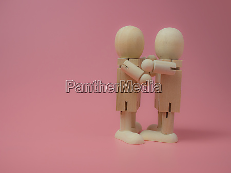2 wooden dolls hugging each other