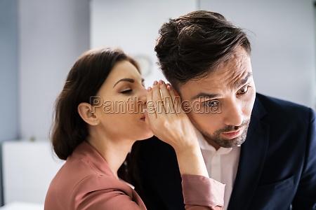 woman whispering gossip in friends ear