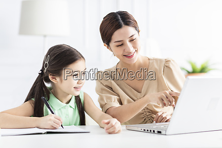 mother with daughter watching the laptop