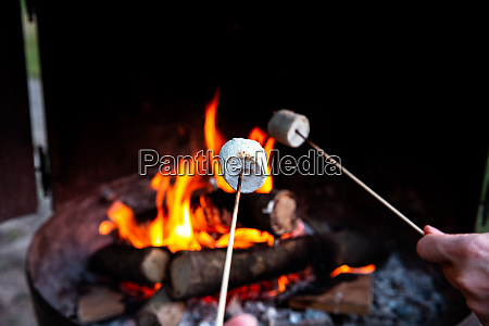 person roasting over fire flames a