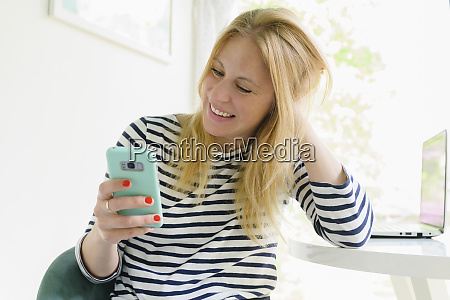 smiling woman using smart phone