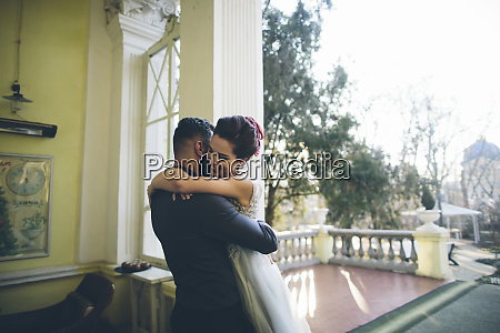newlywed couple embracing at terrace