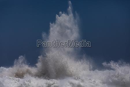 powerful ocean wave breaking against blue