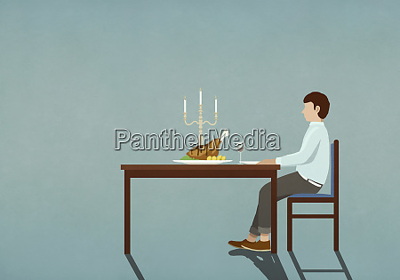 man enjoying candlelight dinner alone at