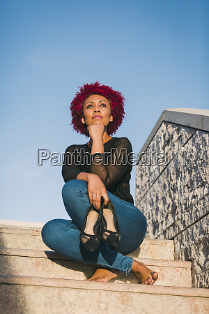 serene woman relaxing on sunny steps