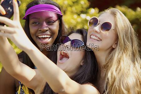 happy teenage girl friends with sunglasses