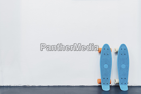blue skateboards leaning against white wall