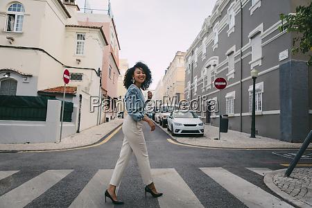 portrait happy stylish woman crossing city