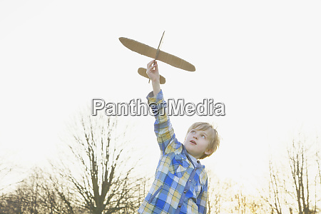 boy playing with cardboard airplane in