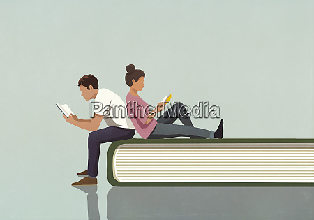 couple reading books on large book