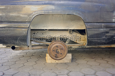 rusted car missing wheel