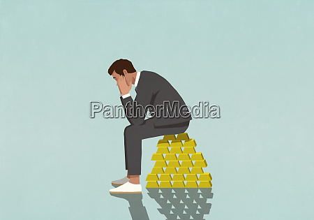 worried male investor sitting on stack