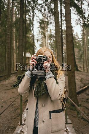 portrait woman using retro camera in