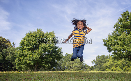portrait playful boy jumping in sunny