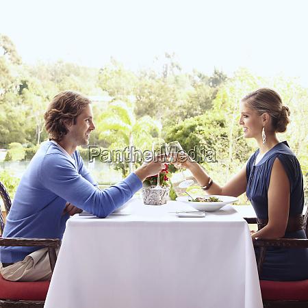 glamorous caucasian couple toasting in restaurant