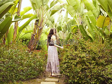 glamorous caucasian woman standing in foliage