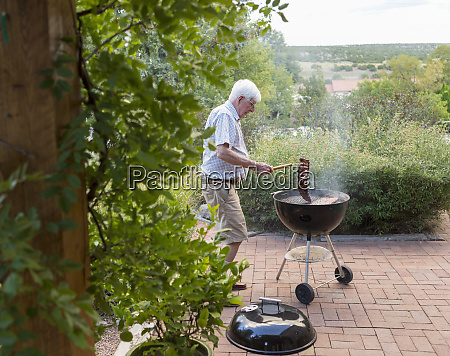 senior man grilling ribs on front