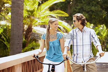 caucasian couple riding bikes over bridge