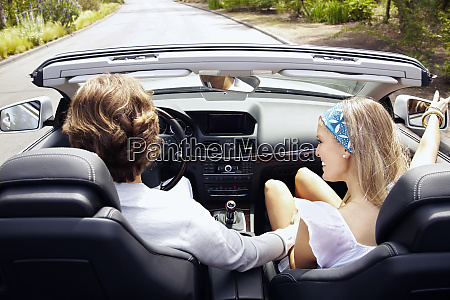 caucasian couple driving in convertible