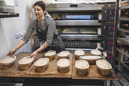 a baker checking proving baskets with