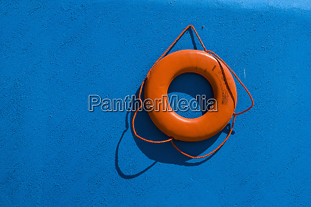 red life preserver against blue wall