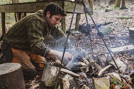 man starting a camp fire in