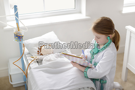 young girl dressed as doctor writing
