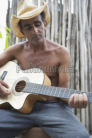 middle aged man playing the guitar