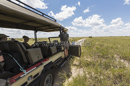 safari guide and vehicle on dirt